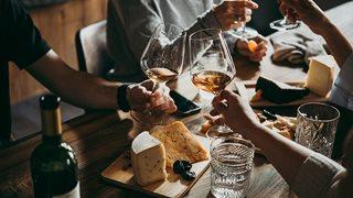 Freunde genießen italienische Kulinarik mit ausreichend Wein und Käse
