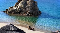 Frau sonnt sich am Sandstrand neben Felsen und glasklarem Wasser