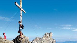 2 Wanderer auf dem Gipfelkreuz auf einem Berg in Korsika