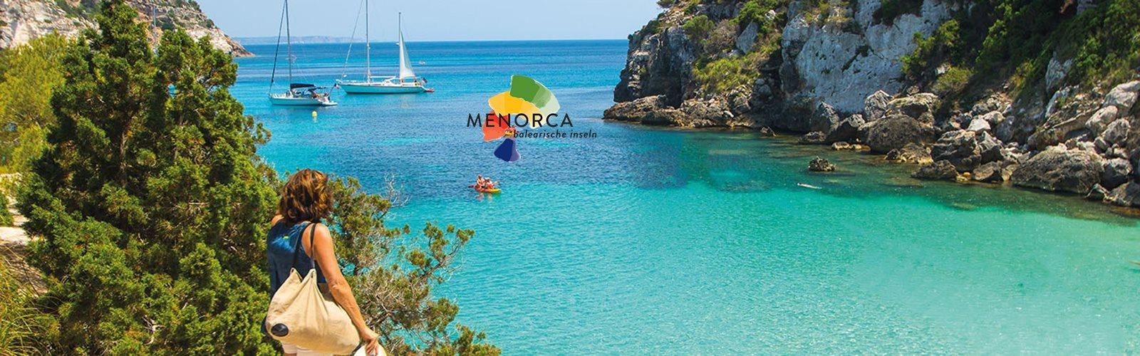 Berühmte Bucht Menorca mit türkisem Meer, grüner Natur und Selgelbooten