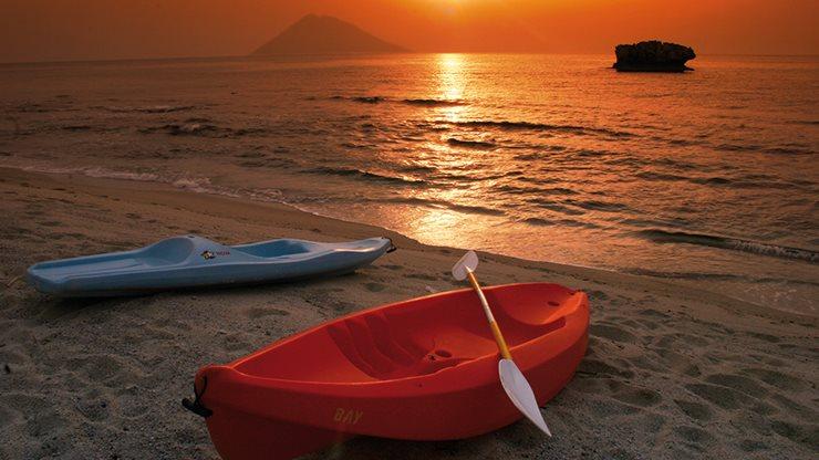 Zwei Paddelboote neben dem Meer mit Sonnenuntergang im Hintergrund