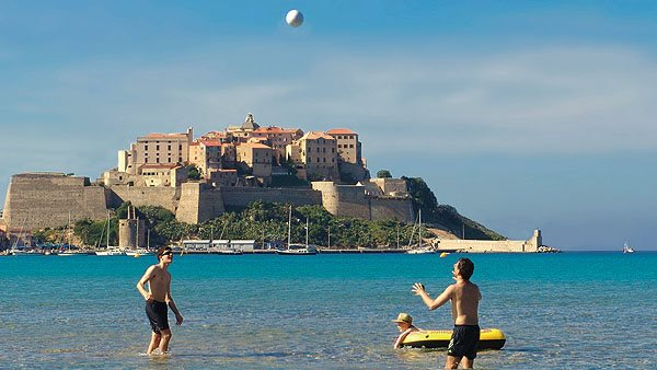 Zwei Urlauber spielen Volleyball am Strand von Calvi im Meer