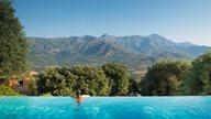 Ein Hotel mit infinity Pool in der Region Calvi mit tollem Blick auf die Berglandschaft Korsikas