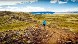 Urlauberin spaziert durch die schier endlos erscheinende natürliche Landschaft Islands