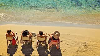 Vier Freunde sitzen in ihren Stühlen am Strand
