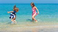 Zwei Kinder spielen und planschen im flachen Teil des Meeres