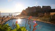 Terrasse mit Pool eines Hotels in Calvi mit Blick aufs Meer und die Festung von Calvi