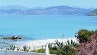 Eine junge Frau spaziert alleine an einem einsamen Strand auf Korsika