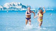Zwei Kinder spielen im Wasser am Strand von Calvi mit der Zitadelle im Hintergrund