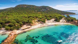 Neben dem türkisblauen Wasser von dem Palombaggia Strand in Korsika erstrecken sich hohe Gebirge