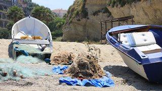 Zwei Fischerboote am Strand neben entladenen Fischernetzen