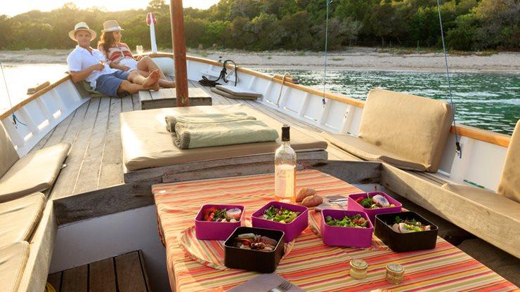 Ein Paar genießt ein Glas Wein in der Abendsonne auf einem Segelboot