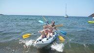 Ein Vater paddelt auf dem Meer in Korsika