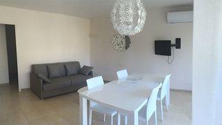 Ein typisch schlichtes Wohnzimmer in Korsika mit gemütlicher Couch und Esstisch