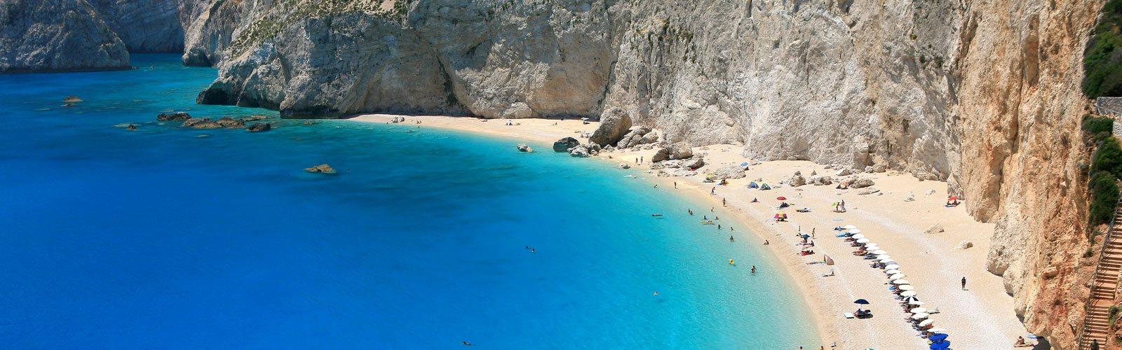 Wunderschöner griechischer Strand mit leuchtendem Meer neben steiler Küstenwand