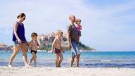 Eine Familie mit 3 kleinen Kindern spaziert am Strand von Calvi