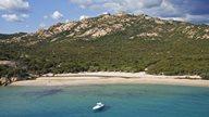 Blaues Meer vor flach abfallendem Strand und üppig grüner Vegetation