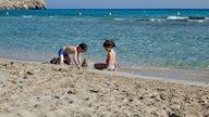 Kinder bauen vor glasklarem Wasser eine Sandburg am Strand